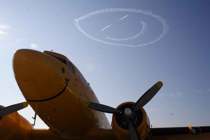 """DC-3 Duggy """"The Smile in the Sky"""" with a smiley face in the background."""