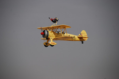 The wingwalker climbs out of the front seat and then hangs in various poses between the upper and lower wing.  At one point she stood on top of the plane which then did a complete loop-de-loop.