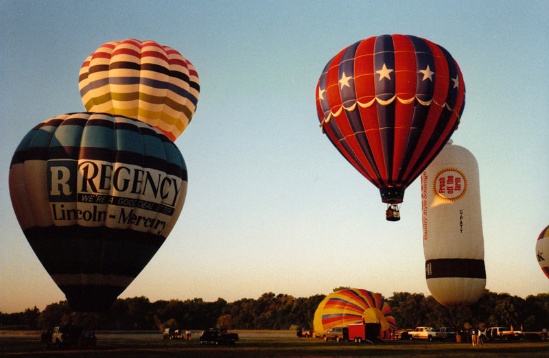 BALLOONS AWAY! The Regency balloon, Lesley Pritchard's <I>Iris</i>, Pebble Rehm's <i>Stars and Stripes</i>, and Jerry Owens' sausage-shaped balloon. Jerry is the man responsible for Owens Country Sausage, hence the shape of the balloon.