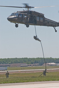 Soldiers rappelling down a Blackhawk