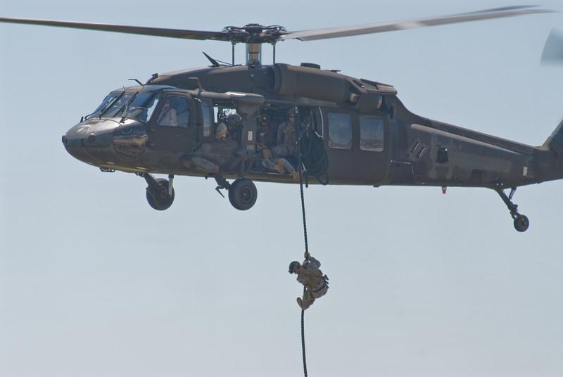 Soldiers rappelling down a Blackhawk