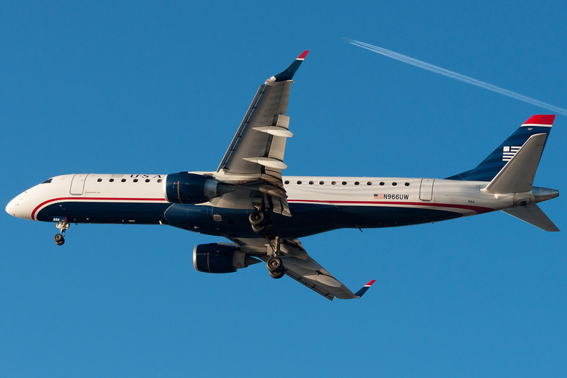 A British Airways 747 is making that contrail as this US Airways E-190 is on final for runway 27.