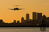 An AirTran 717 is on short final for runway 27 at BOS in the sunset.