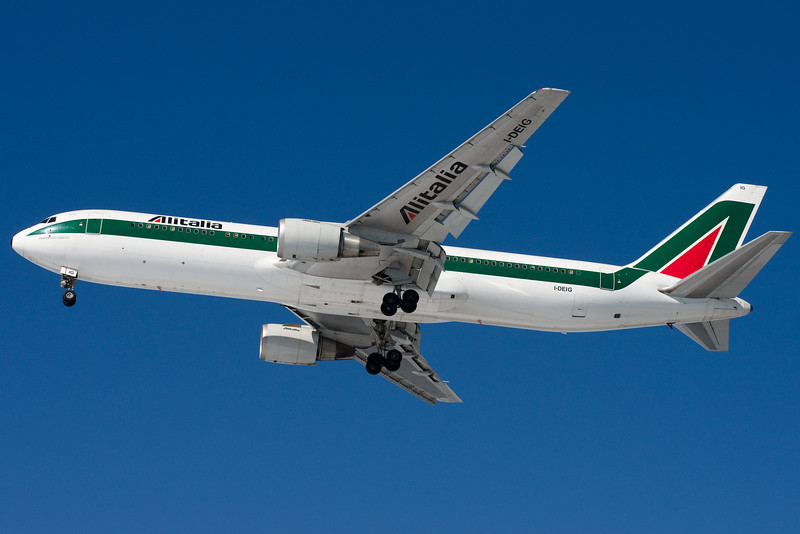 The snow lights up the underside of this Alitalia heavy.