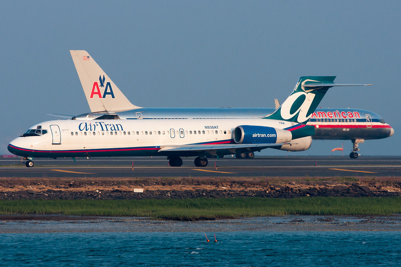 As this AirTran jet taxis, an American 757 behind it departs.