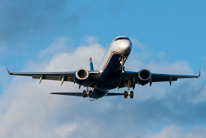 A Nose-on view of a US Airways E-190 on final for runway 27.