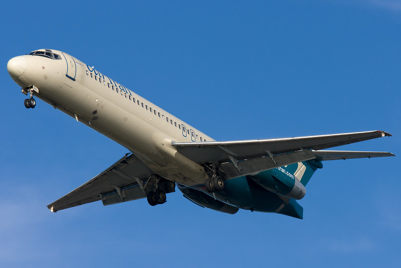 An AirTran 717 in old scheme on final to runway 27.