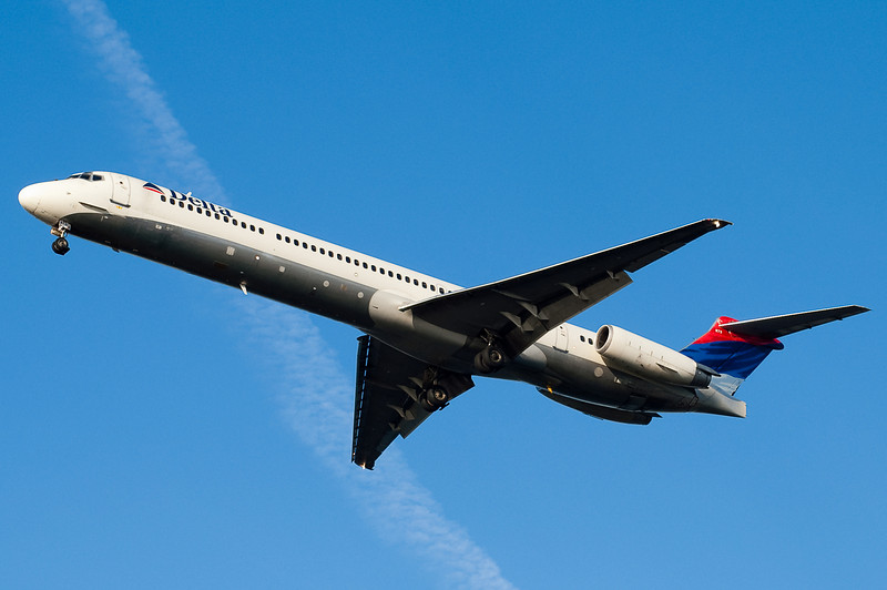 This DL MD-88 is on final for 27 with a contrail crossing.
