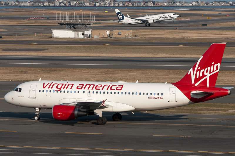 This Virgin American A319 taxis to its gate as an Alaska 737-800 departs on runway 22L.