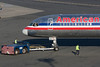 The ground crew is ready to detach the towbar from this American 757 as it readies for departure.