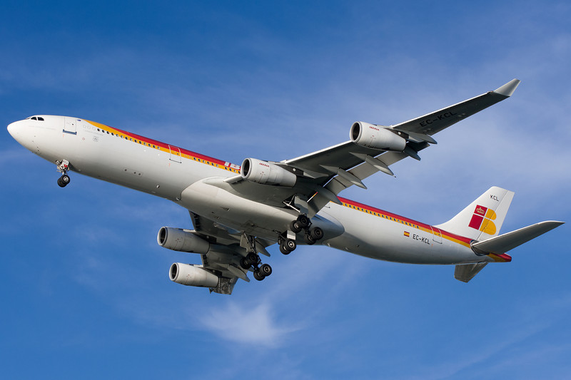 Ibera's A340-300 on final for runway 27 with some white puffy clouds in the background.