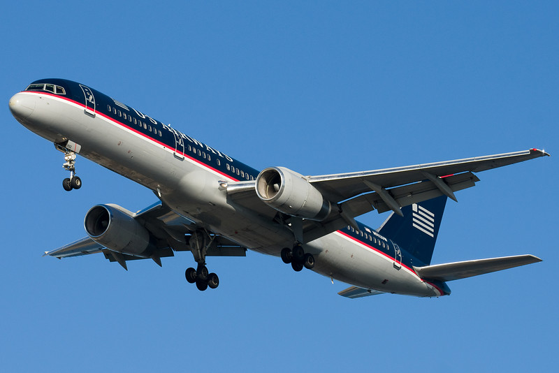 A US 757 in desperate need of paint is on final for 27.