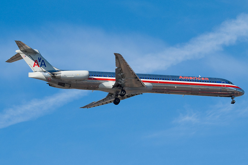Contrails and cloud whisps for this American MD-82.