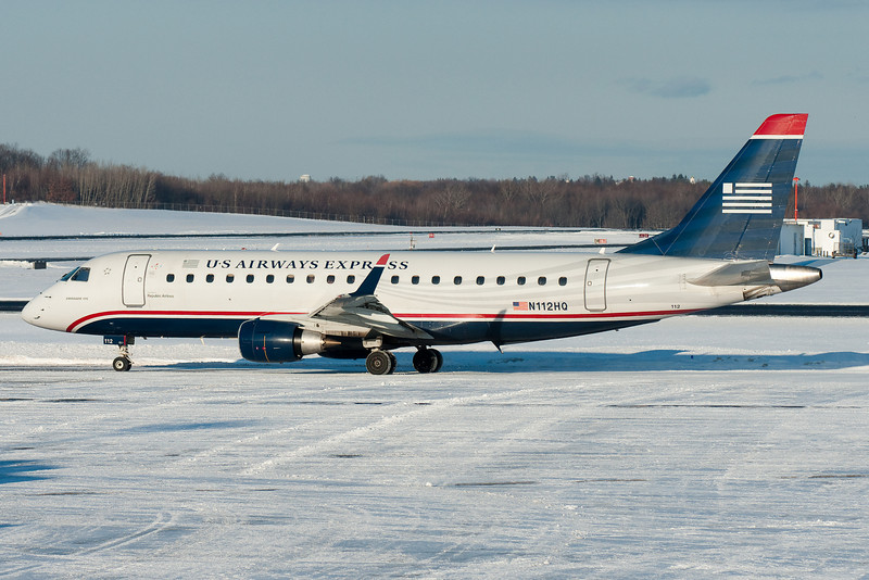 This US Airways Express E-175 is off towards runway 6 for takeoff on a snowy Sunday.