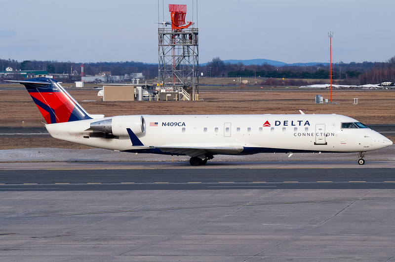 A Delta Connection CRJ is taxiing towards the terminal.