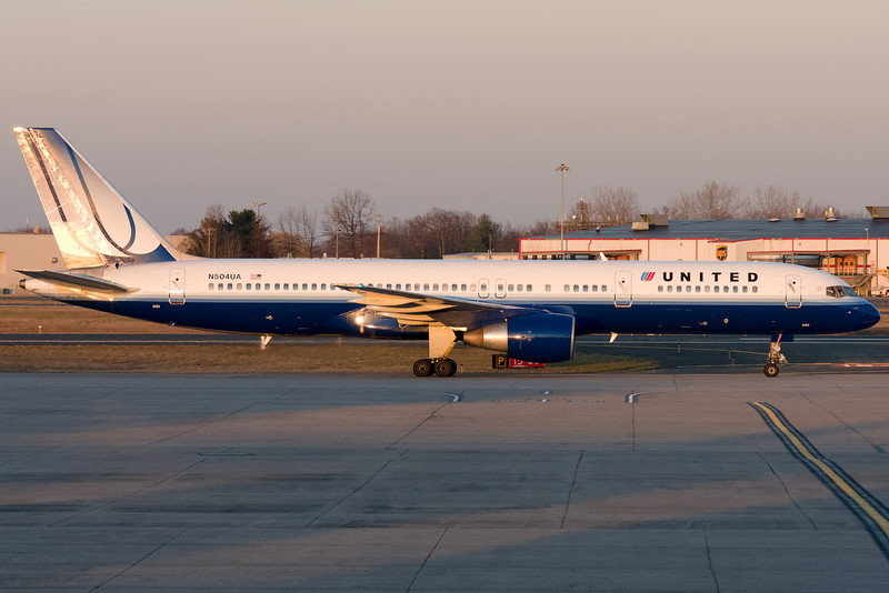 The United 757 from Chicago taxis to the gate as the sun fades away.