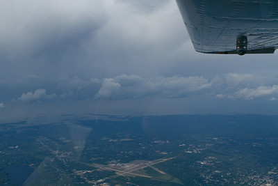 Passing to the east of scuddy clouds south of Boston.