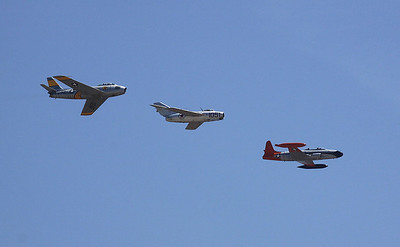 Korean War era F-86, MIG-15 and T-33 jets make a group flyby.