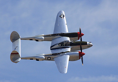 A Lockheed P-38L Lightning banking during a flyby.