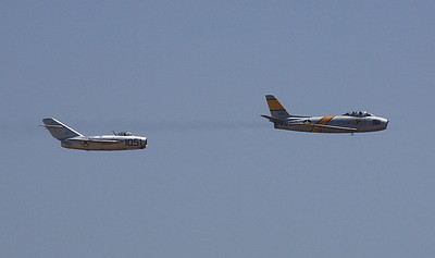 Former Korean War adversaries, the MIG-15 and F-86 Saber, make a tandem flyby.