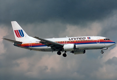 United Airlines Boeing 737-322  	Miami - Intl. (Wilcox Field / 36th Street / Pan American Field) (MIA / KMIA) USA - Florida, November 1993 Reg: N335UA  Cn: 24230/1607 Approaching RWY 09R under stormy skies.