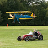 The 1937 Sprint Car beats the Stearman in the race around the airfield.