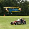The 1937 Sprint Car beats the Stearman in the race around the airfield.