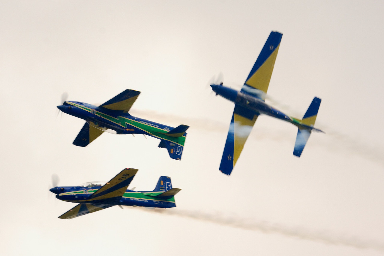 The rightmost aircraft is actually doing a series of rolls around the 5 and 6 aircraft formation.  The Força Aérea Brasileira Esquadrilha da Fumaça (Brazilian Air Force Smoke Squadron)