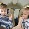 """Daniel Pushkarev, 8, of Brookline, and Thomas Lipnesh, 8, of Wayland, prepare for a plane ride with Russ """"Toby"""" Hume, of the Fitchburg Pilot's Association during the Fitchburg Municipal Airport's 85th Anniversary celebration on Saturday afternoon. SENTINEL & ENTERPRISE / Ashley Green"""