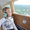 """Thomas Lipnesh, 8, of Wayland, looks out the window while on a plane ride with Russ """"Toby"""" Hume, of the Fitchburg Pilot's Association during the Fitchburg Municipal Airport's 85th Anniversary celebration on Saturday afternoon. SENTINEL & ENTERPRISE / Ashley Green"""