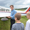 """Russ """"Toby"""" Hume, of the Fitchburg Pilot's Association, prepares Daniel Pushkarev, 8, of Brookline, and Thomas Lipnesh, 8, of Wayland, for a plane ride during the Fitchburg Municipal Airport's 85th Anniversary celebration on Saturday afternoon. SENTINEL & ENTERPRISE / Ashley Green"""