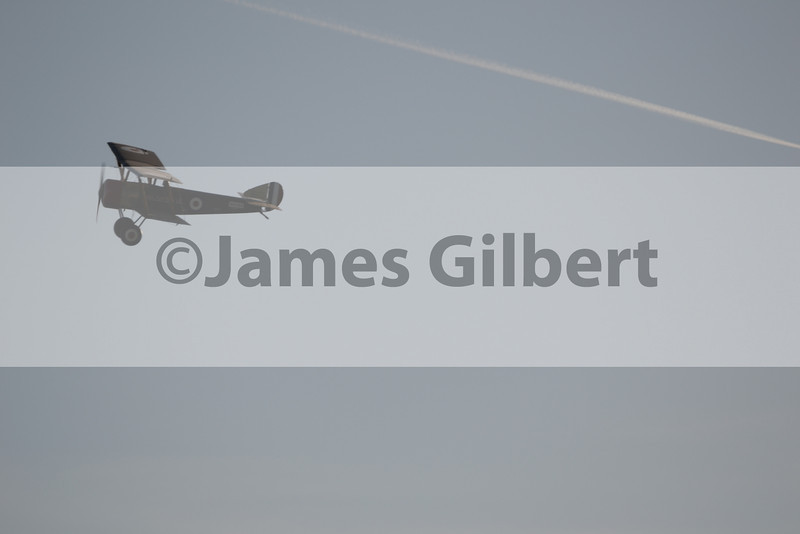 Just the right time for the biplane to cross the contrail of a modern jet airliner!