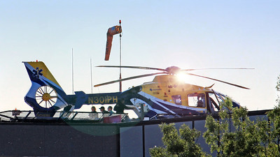 MedForce One on the rooftop helipad at UIHC.  Randy Wolfe (ball cap), flight paramedic. This image was taken around 6:30 pm., a time of day where capturing helipad images are almost impossible due to the angle of the Sun.