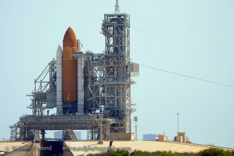 """Endeavour on the launch pad.  Shot this a few weeks before the launch.  The RSS (Rotating Service Structure) still surrounds Endeavour so you can't see it.  Notice the """"scars"""" on the orange tank.  This tank has a few nicknames including """"The Katrina Tank"""".  The tank was sitting in the assembly facility in New Orleans when Katrina hit and the building collapsed around it.  The scars (lighter orange) that you see are areas where the tank was repaired and the difference in color is because that is newer insulation than the rest.  The color gets a deeper orange the longer it sits in the sun, it kind of gets a sun tan so the newer areas are lighter."""