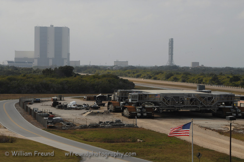 A shot eastbound from the observation gantry.  In the foreground is one of the two crawler transports used to move the shuttles from the Vehicle Assembly (VAB) building to the launch pads.  The large square building on the left is the VAB where the shuttles are matted to the fuel tank and the solid rocket boosters.  The tall tower on the right was built for the Constellation program that was supposed to come after the Space Shuttle but is now cancelled.