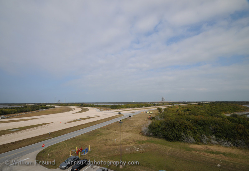 """View from the observation gantry looking out towards the two launch pads.  On the right is 39A and on the left further back is the remnants of 39B.  The wide gravel roads that you see are the """"roads"""" used by the crawler transport."""