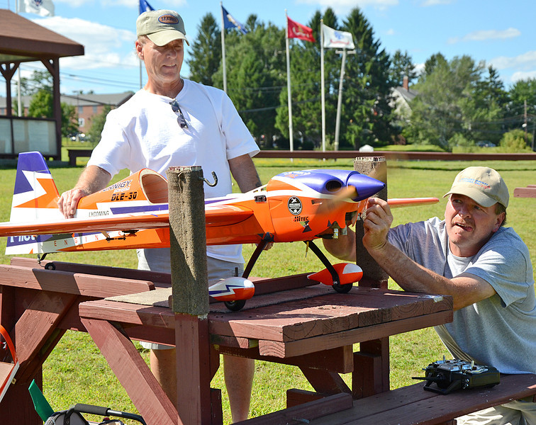 Bob Palermo, of Chelmsford, and Jim Dawe, of Billerica, work on a remote controlled plane before taking flight at Vietnam Veterans Park in Billerica on Sunday afternoon. They are both part of the Middlesex County R/C Flyers Club. (SUN/Ashley Green)