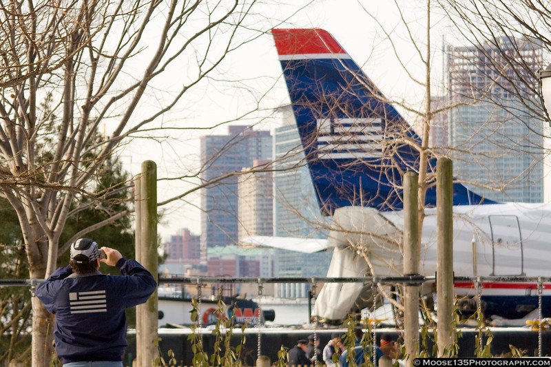 US Airways worker photographing their damaged aircraft.