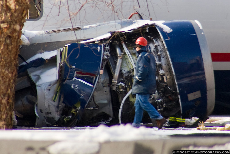 Recovery worker stands next to the damaged right-side engine.