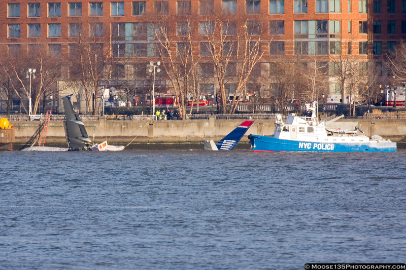 A NYC Police boat stands guard near the remains of the aircraft.