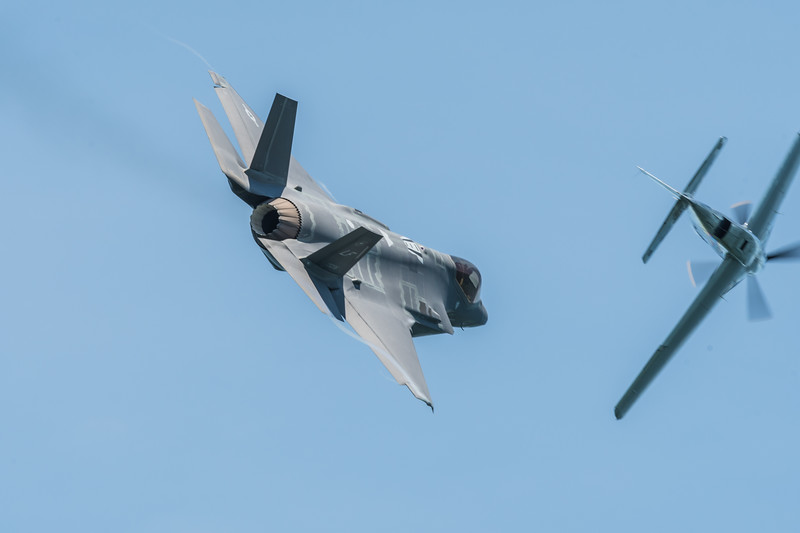 F-35 banking right with a P-51 D going left