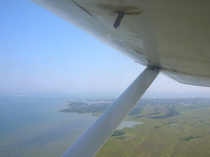 in 2003 I took my biannual flight review from the local fella that runs an air taxi on the island so I rent one of his planes when we go.  Just took off from the airstrip and the village (greener area) is on the sound.