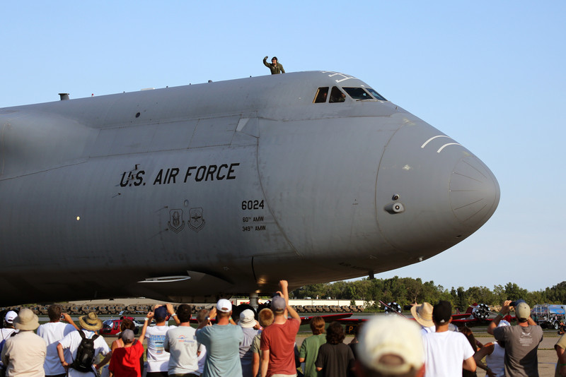 "A U.S. Air Force crewman waves ""Hello"" from atop a giant C-5 at the EAA Air Adventure 2012."