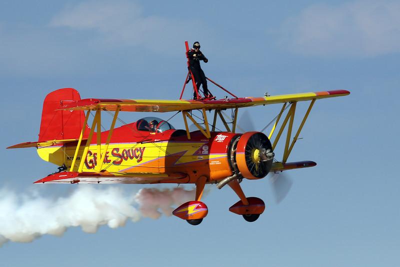 Teresa Stokes waving from the top of Gene Soucy's Grumman Ag Cat bi-plane