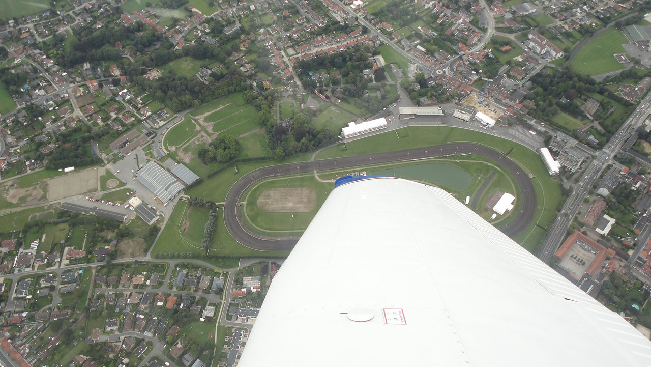 """Celebrating another """"on time and on track"""" arrival over my turning point: the Waregem racetrack. One orbit to the right, allowing my passenger to take this shot."""
