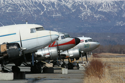 Palmer Airport. Old DC 3 ?  Planes  If you know what they are please let me know. Thanks. Notice the concrete block the planes are tied too. It is because of the wind that Palmer gets every winter. The wind would move the planes or flip them over.