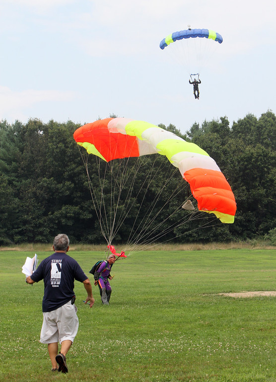 . Skydivers over 60 and over 70 attempt to set New England group records, flying out of Skydive Pepperell. Organizer George Burliss of Hollis, N.H., foreground, welcomes Skip Kniley, 72, of Columbus, Ohio, who\'d just landed. (SUN/Julia Malakie)