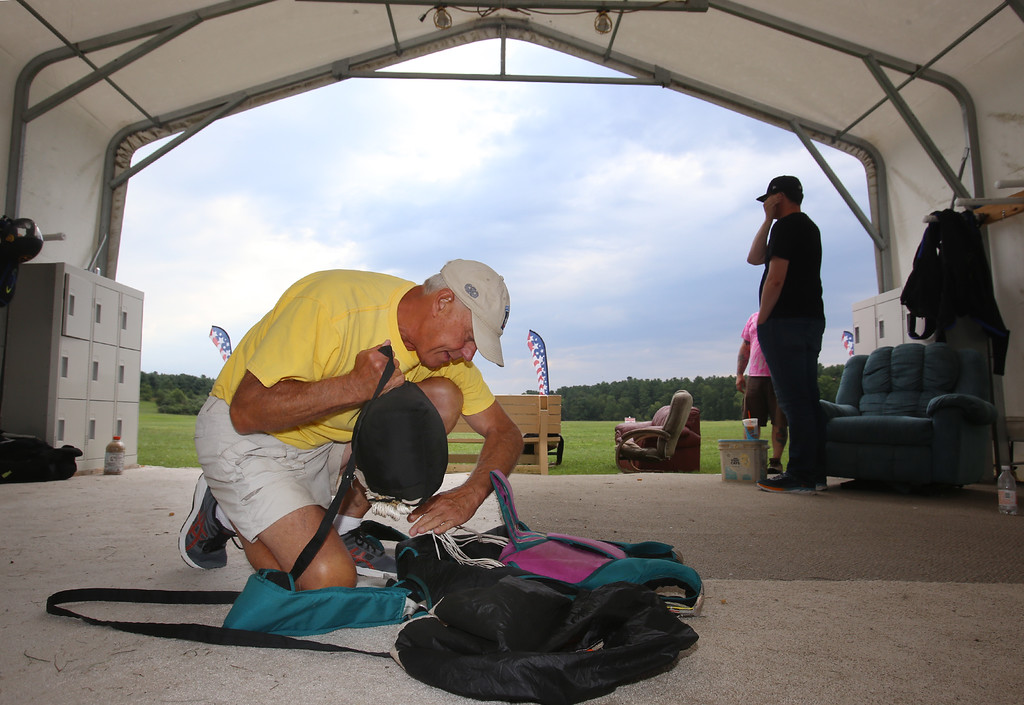 . Skydivers over 60 and over 70 attempt to set New England group records, flying out of Skydive Pepperell. Skip Kniley, 72, of Columbus, Ohio, packs his parachute. (SUN/Julia Malakie)