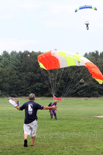 Skydivers over 60 and over 70 attempt to set New England group records, flying out of Skydive Pepperell. Organizer George Burliss of Hollis, N.H., foreground, welcomes Skip Kniley, 72, of Columbus, Ohio, who'd just landed. (SUN/Julia Malakie)