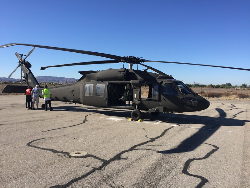 Military Blackhawk flew in and landed far away from the rest of the airplanes.